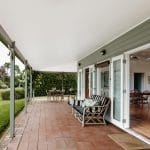 Large undercover verandah with cushioned couch and view to garden